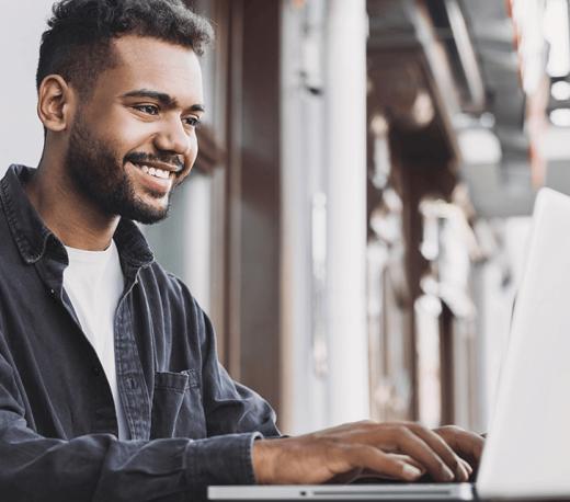 Guy writing on his laptop smiling