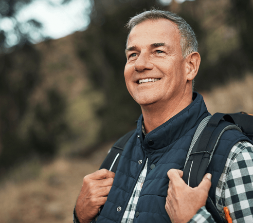 Older man outside with a backpack on, smiling