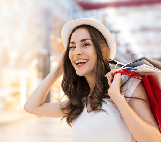 Woman with brown hair and a hat holding shopping bags behind her back, laughing