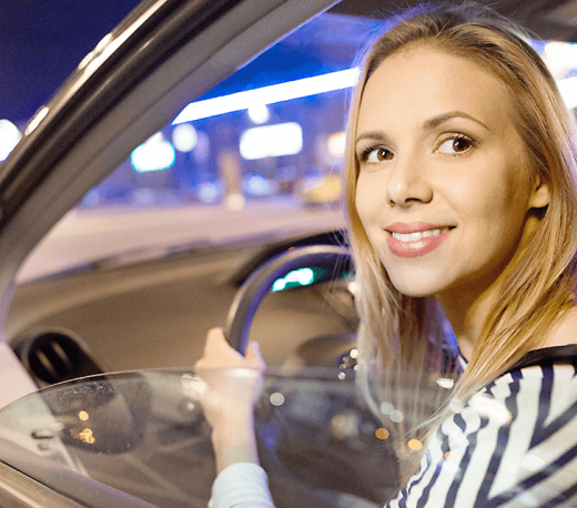 Blonde girl smiling, driving a car while looking back